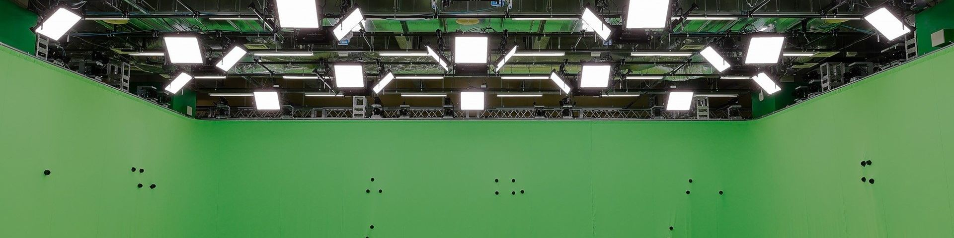 The ceiling and walls of the new Canon Volumetric Video studio in Kawasaki, Japan. The walls are green and have small, round black objects protruding from them at seemingly random positions and intervals. Above are more than two dozen flat square lights hanging from a rig below the ceiling.
